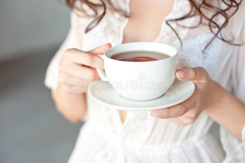 Κινηματογράφηση σε πρώτο πλάνο ενός άσπρου φλυτζανιού του καυτού καφέ τέχνης latte με μια μορφή καρδιών στα χέρια ενός νέου κοριτ στοκ εικόνα