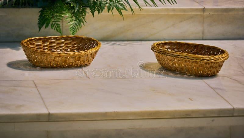 Κινηματογράφηση σε πρώτο πλάνο ενός εκλεκτής ποιότητας ψάθινου καλαθιού στο μαρμάρινο πάτωμα μιας καθολικής εκκλησίας έτοιμης να  στοκ φωτογραφία με δικαίωμα ελεύθερης χρήσης