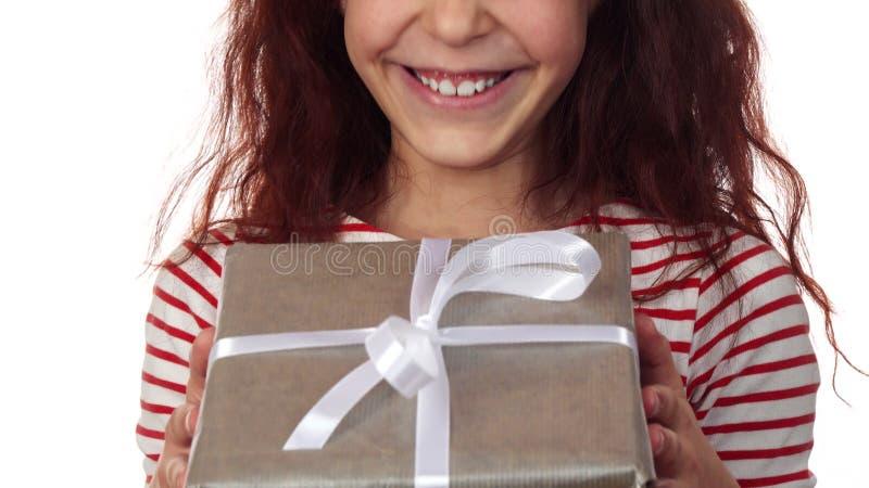 Κινηματογράφηση σε πρώτο πλάνο ενός ευτυχούς προσώπου κοριτσιών με ένα νέο δώρο έτους στα χέρια στοκ εικόνες