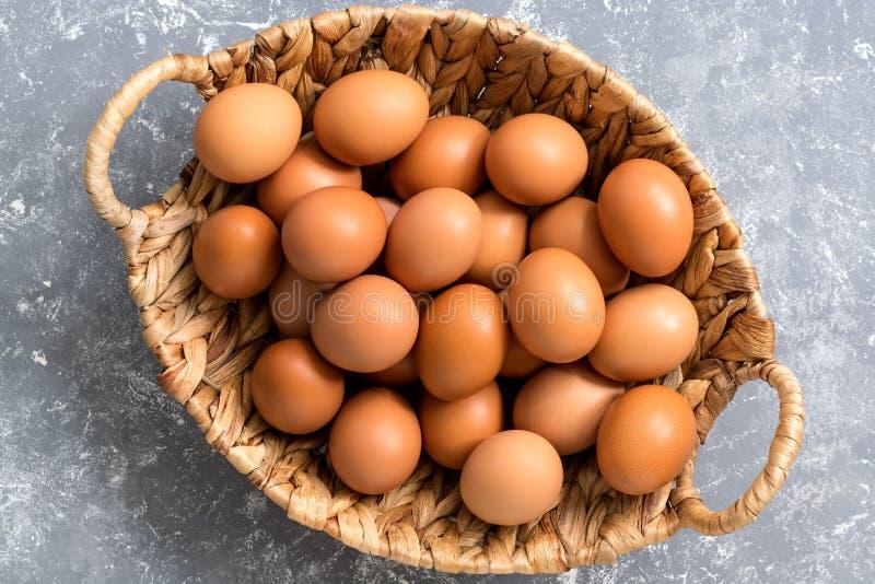 Κινηματογράφηση σε πρώτο πλάνο ενός καφετιού αυγού κοτόπουλου σε ένα καλάθι σε ένα γκρίζο υπόβαθρο Η τοπ άποψη, επίπεδη βάζει στοκ εικόνες