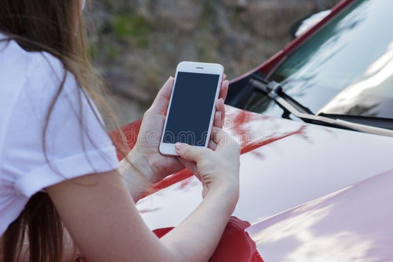 Κινηματογράφηση σε πρώτο πλάνο ενός κοριτσιού που κρατά ένα smartphone στην κουκούλα ενός αυτοκινήτου στοκ φωτογραφίες με δικαίωμα ελεύθερης χρήσης