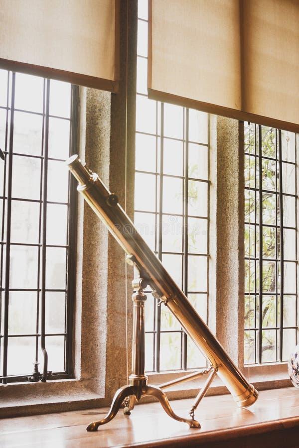 Κινηματογράφηση σε πρώτο πλάνο ενός μεγάλου εκλεκτής ποιότητας τηλεσκοπίου σε ένα windowsill μέσα σε ένα σπίτι στοκ εικόνες