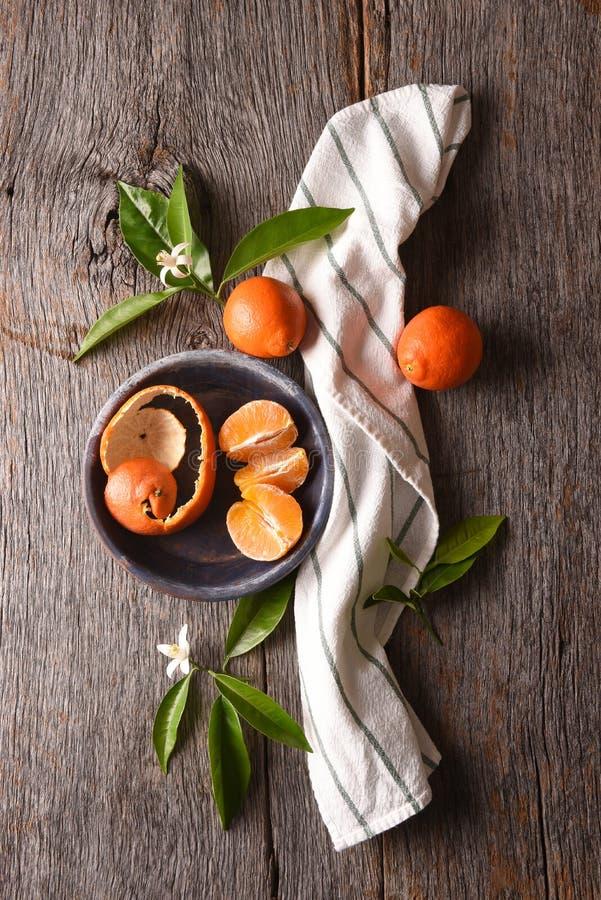 Κινηματογράφηση σε πρώτο πλάνο ενός ξεφλουδισμένου πορτοκαλιού σε ένα πιάτο με την πετσέτα και των φύλλων σε έναν αγροτικό ξύλινο στοκ φωτογραφία με δικαίωμα ελεύθερης χρήσης