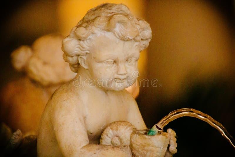 Κινηματογράφηση σε πρώτο πλάνο ενός παλαιού αγάλματος ενός παιδιού και μια πηγή με ένα θολωμένο υπόβαθρο στοκ εικόνες