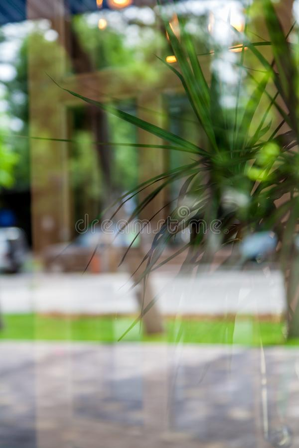 Κινηματογράφηση σε πρώτο πλάνο ενός παραθύρου με μια αντανάκλαση της οδού και ενός καφέ έξω από το παράθυρο στοκ φωτογραφία με δικαίωμα ελεύθερης χρήσης