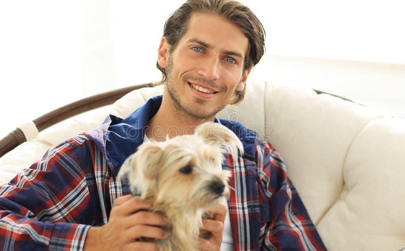 Κινηματογράφηση σε πρώτο πλάνο ενός τύπου χαμόγελου που κτυπά το σκυλί του καθμένος σε μια μεγάλη πολυθρόνα στοκ φωτογραφίες