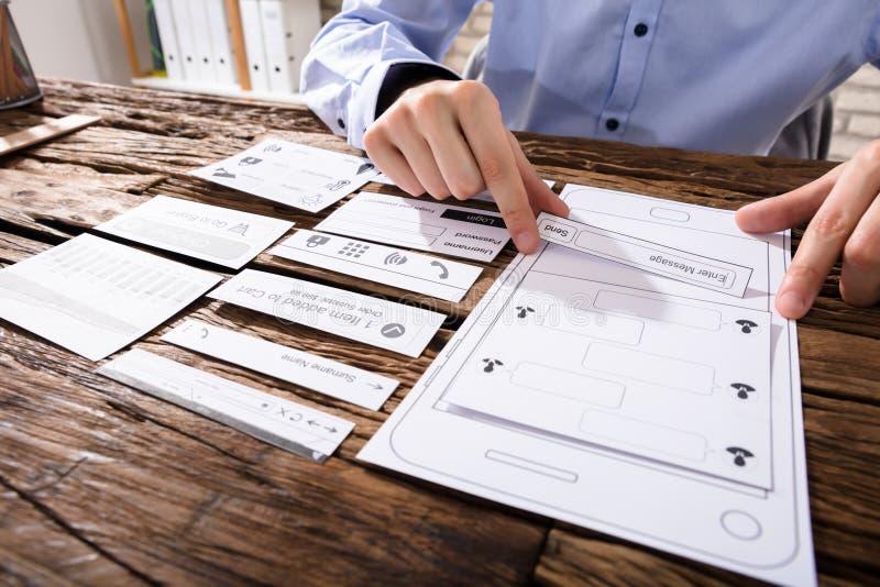 Κινηματογράφηση σε πρώτο πλάνο ενός χεριού σχεδιαστών ` s που σχεδιάζει την κινητή εφαρμογή στοκ φωτογραφία
