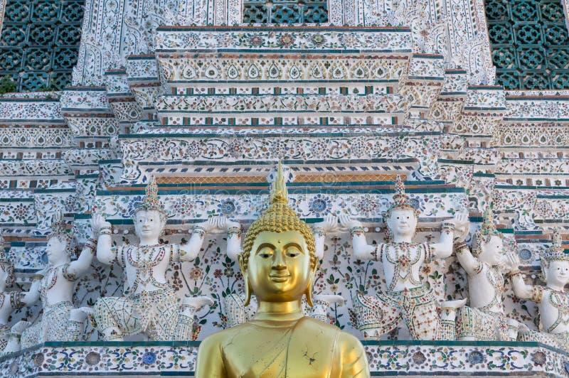 Κινηματογράφηση σε πρώτο πλάνο ενός χρυσού αγάλματος του Βούδα μπροστά από ένα ψηλό κτίριο σε Wat Arun στοκ φωτογραφία