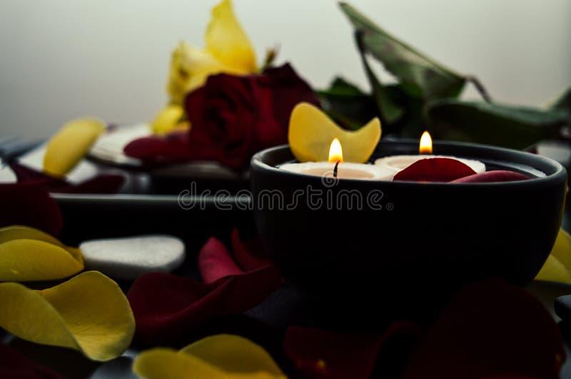 Κινηματογράφηση σε πρώτο πλάνο ενός όμορφου ρομαντικού γεύματος με τα πέταλα λουλουδιών, τριαντάφυλλα, κεριά βαλεντίνος ημέρας s στοκ φωτογραφία