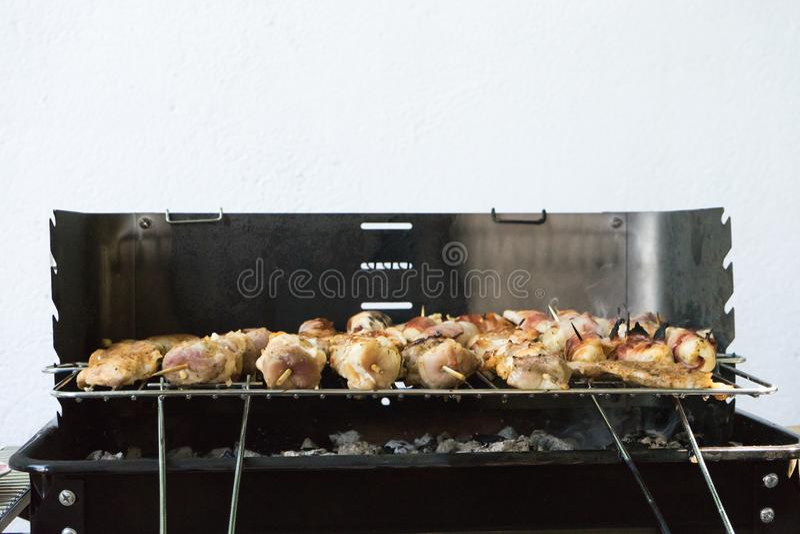 κινηματογράφηση σε πρώτο πλάνο κάποιου κρέατος στα ξύλινα οβελίδια που ψήνονται στη σχάρα σε μια σχάρα Ψήσιμο στη σχάρα που μαριν στοκ εικόνα με δικαίωμα ελεύθερης χρήσης