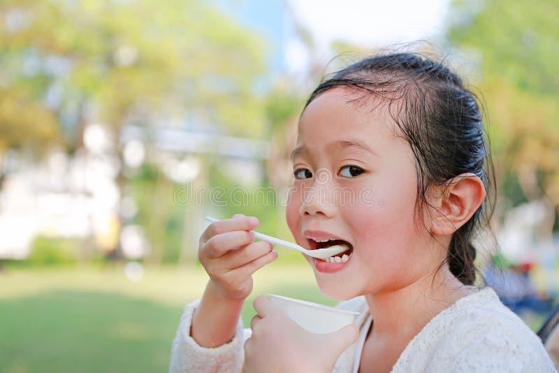 Κινηματογράφηση σε πρώτο πλάνο λίγο ασιατικό κορίτσι παιδιών που τρώει το γιαούρτι στο πάρκο στοκ εικόνες