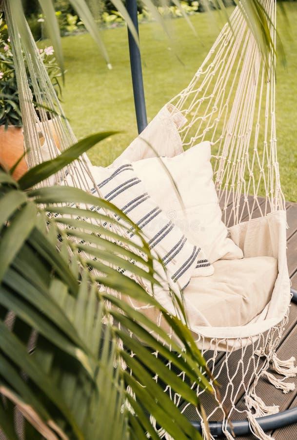 Κινηματογράφηση σε πρώτο πλάνο μιας αιώρας boho που κρεμά σε έναν ηλιόλουστο κήπο με έναν φοίνικα στοκ εικόνες