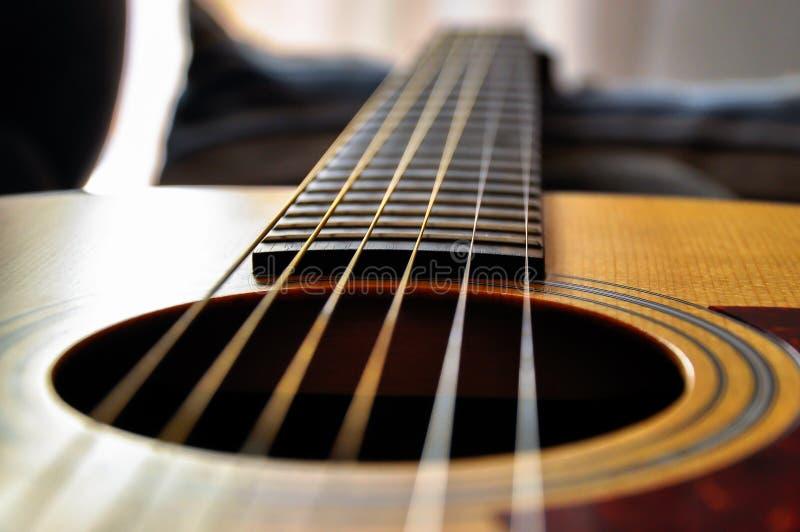 Κινηματογράφηση σε πρώτο πλάνο μιας ακουστικής κιθάρας στοκ εικόνες