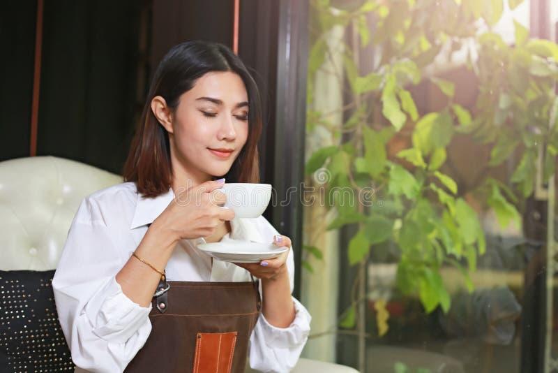 Κινηματογράφηση σε πρώτο πλάνο μιας ασιατικής γυναίκας που κρατά και που πίνει τον καυτό καφέ με το Φε στοκ εικόνες με δικαίωμα ελεύθερης χρήσης
