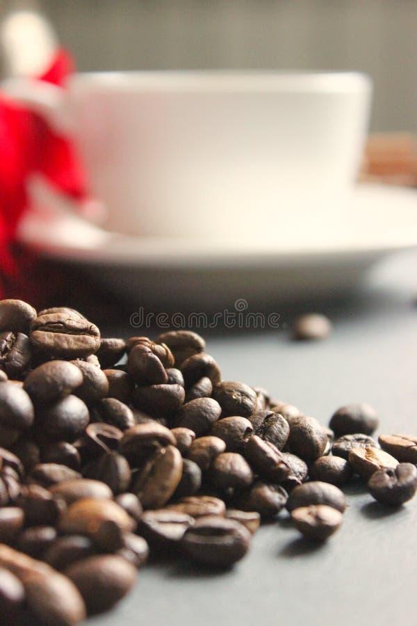 Κινηματογράφηση σε πρώτο πλάνο μιας δέσμης των φασολιών καφέ που διασκορπίζονται στον πίνακα στοκ φωτογραφίες