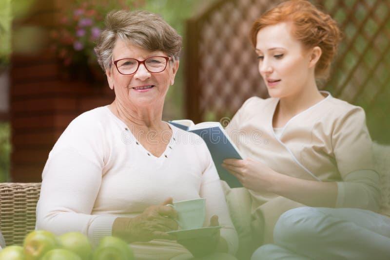 Κινηματογράφηση σε πρώτο πλάνο μιας ευτυχούς ανώτερης γυναίκας και ενός νέου επαγγελματικού NU της στοκ εικόνες