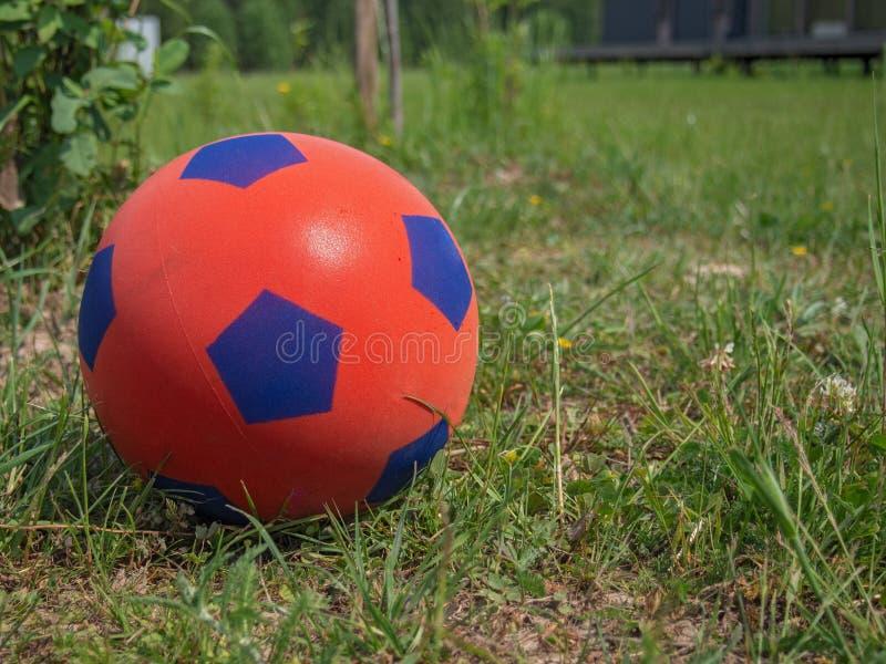 Κινηματογράφηση σε πρώτο πλάνο μιας κόκκινης σφαίρας ποδοσφαίρου για τα παιδιά στην πράσινη χλόη μπροστά από ένα εξοχικό σπίτι r στοκ φωτογραφία με δικαίωμα ελεύθερης χρήσης
