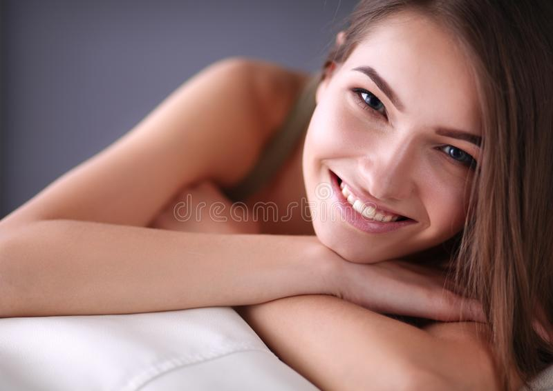 Κινηματογράφηση σε πρώτο πλάνο μιας χαμογελώντας νέας γυναίκας που βρίσκεται στον καναπέ στοκ φωτογραφία