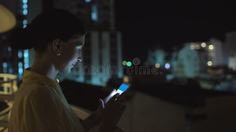 Κινηματογράφηση σε πρώτο πλάνο νέο γυναικών χαμόγελου στο smartphone που στέκεται στο πεζούλι στεγών τη νύχτα στοκ εικόνες με δικαίωμα ελεύθερης χρήσης