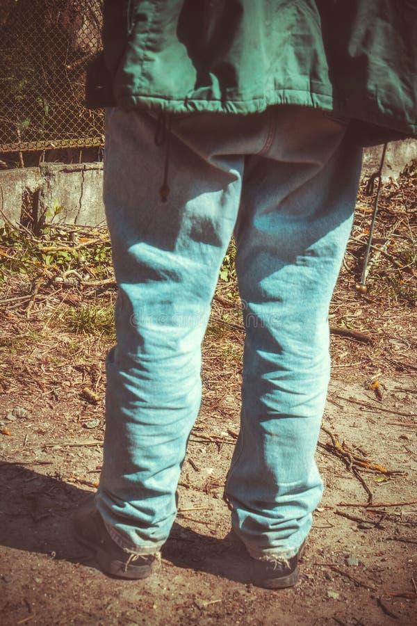 Κινηματογράφηση σε πρώτο πλάνο οπισθοσκόπος των ποδιών ενός ατόμου στο παλαιό τζιν παντελόνι και τα παλαιά παπούτσια βαμμένος στοκ εικόνες