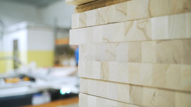Κινηματογράφηση σε πρώτο πλάνο πολλών ξύλινων ξύλινων φραγμών σε ένα εργαστήριο και μια θολωμένη σκιαγραφία του ατόμου που λειτου στοκ φωτογραφία με δικαίωμα ελεύθερης χρήσης