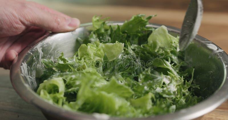 Κινηματογράφηση σε πρώτο πλάνο που αναμιγνύει τα φύλλα σαλάτας frillis με τη caesar σάλτσα στοκ εικόνες με δικαίωμα ελεύθερης χρήσης