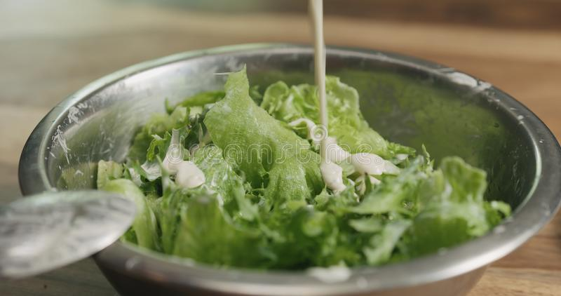 Κινηματογράφηση σε πρώτο πλάνο που αναμιγνύει τα φύλλα σαλάτας frillis με τη caesar σάλτσα στοκ φωτογραφίες