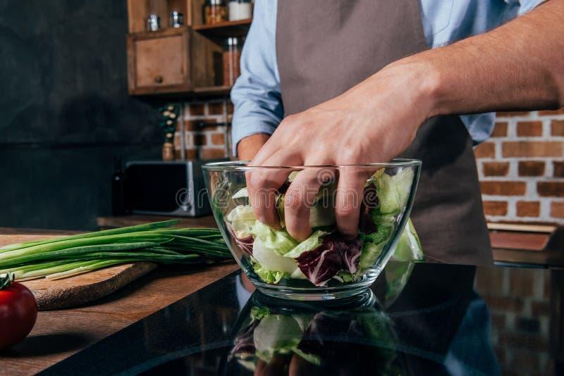 κινηματογράφηση σε πρώτο πλάνο που βλασταίνεται του ατόμου που αναμιγνύει τη σαλάτα με τα χέρια στοκ εικόνα