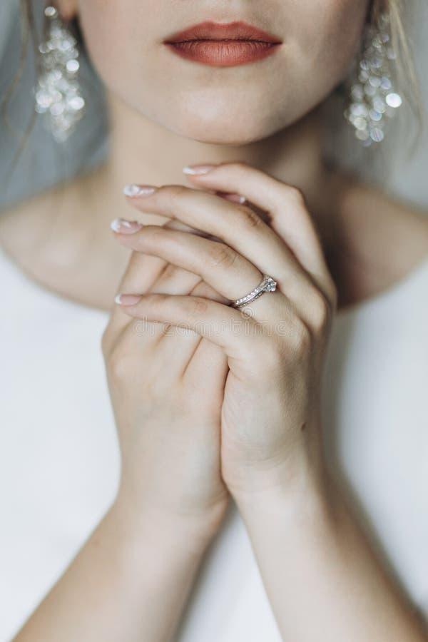 Κινηματογράφηση σε πρώτο πλάνο που πυροβολείται μιας κομψής, νύφης brunette στα εκλεκτής ποιότητας άσπρα dres στοκ εικόνα