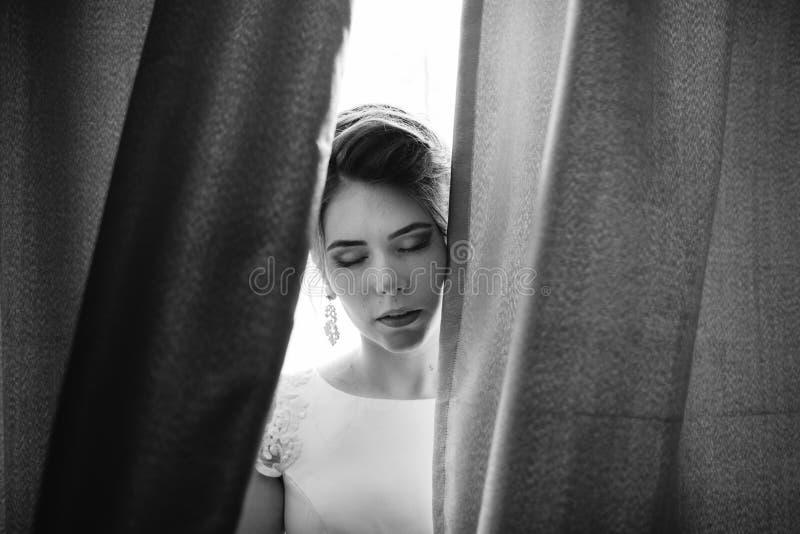 Κινηματογράφηση σε πρώτο πλάνο που πυροβολείται μιας κομψής, νύφης brunette στα εκλεκτής ποιότητας άσπρα dres στοκ φωτογραφίες