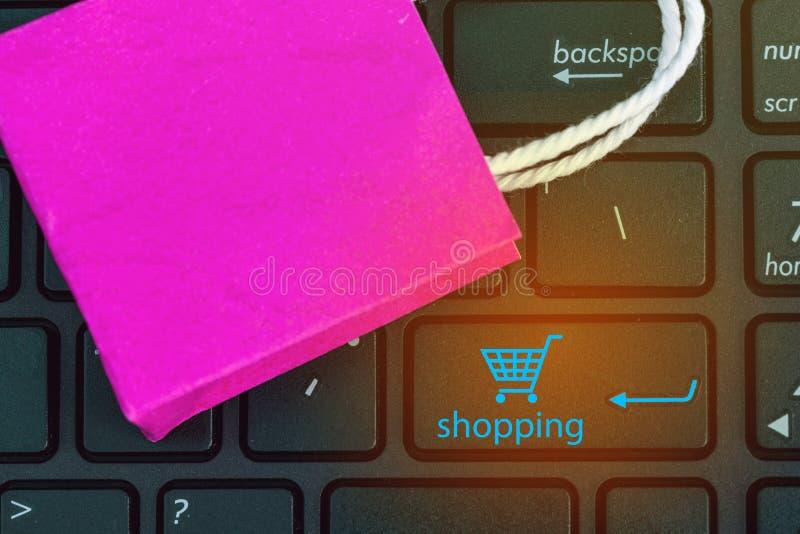 Κινηματογράφηση σε πρώτο πλάνο που πυροβολείται της ρόδινης τσάντας αγορών εγγράφου στο πληκτρολόγιο σημειωματάριων E στοκ εικόνες