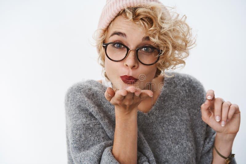 Κινηματογράφηση σε πρώτο πλάνο που πυροβολείται της χαριτωμένης όμορφης ξανθής σγουρός-μαλλιαρής γυναίκας στα γυαλιά beanie και τ στοκ φωτογραφία