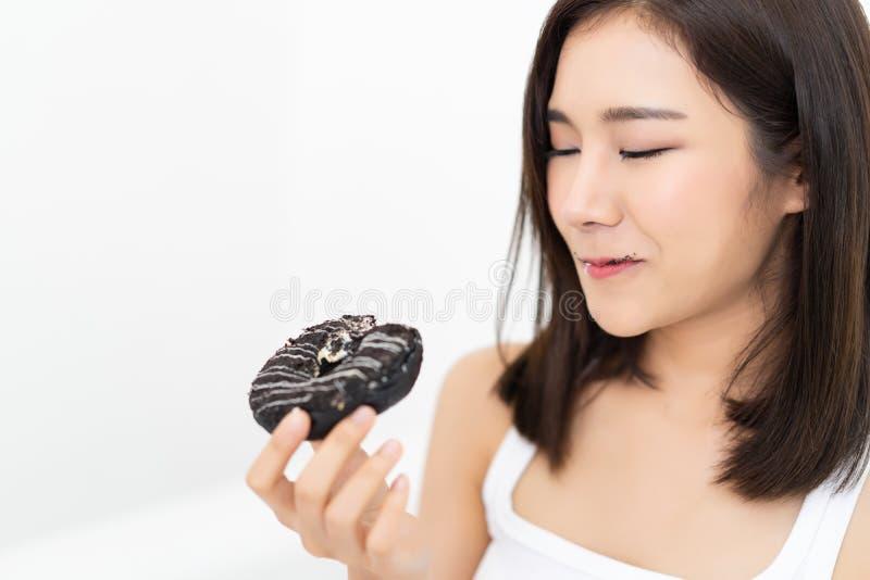 Κινηματογράφηση σε πρώτο πλάνο που χαμογελά τη νέα ασιατική γυναίκα που τρώει τη σοκολάτα donuts που κάνει στοκ φωτογραφίες