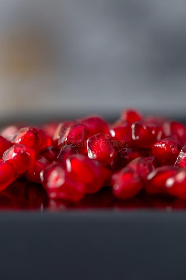 Κινηματογράφηση σε πρώτο πλάνο σπόρων ροδιών Γκρίζο υπόβαθρο και κόκκινα σιτάρια granate r r στοκ φωτογραφία