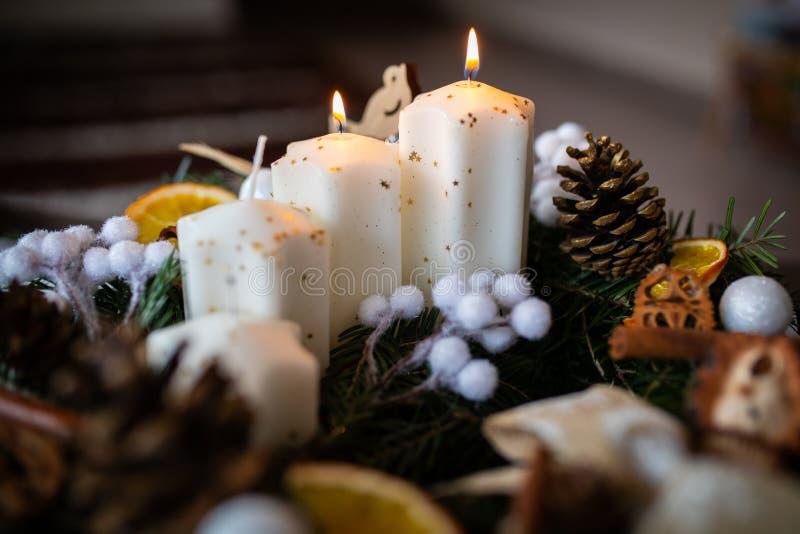 Κινηματογράφηση σε πρώτο πλάνο στεφανιών Χριστουγέννων εμφάνισης με τα κεριά στοκ εικόνα