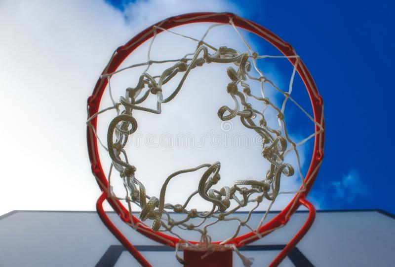 Κινηματογράφηση σε πρώτο πλάνο στη στεφάνη καλαθοσφαίρισης που ανατρέχει από κάτω από ενάντια σε έναν μπλε ουρανό στοκ φωτογραφίες