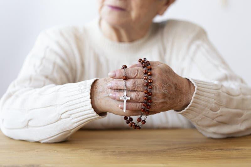 Κινηματογράφηση σε πρώτο πλάνο στο ανώτερο πρόσωπο χέρια του s με rosary και cros στοκ φωτογραφίες με δικαίωμα ελεύθερης χρήσης