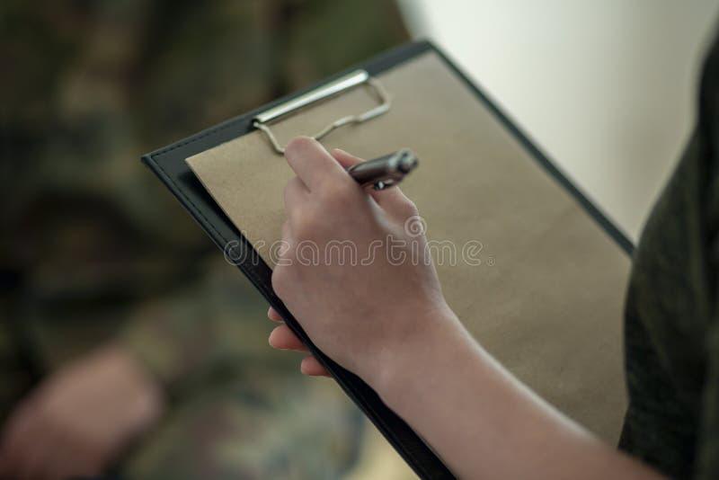 Κινηματογράφηση σε πρώτο πλάνο στο θεράποντα που κάνει τις σημειώσεις για το κομμάτι χαρτί κατά τη διάρκεια του διορισμού στοκ φωτογραφίες