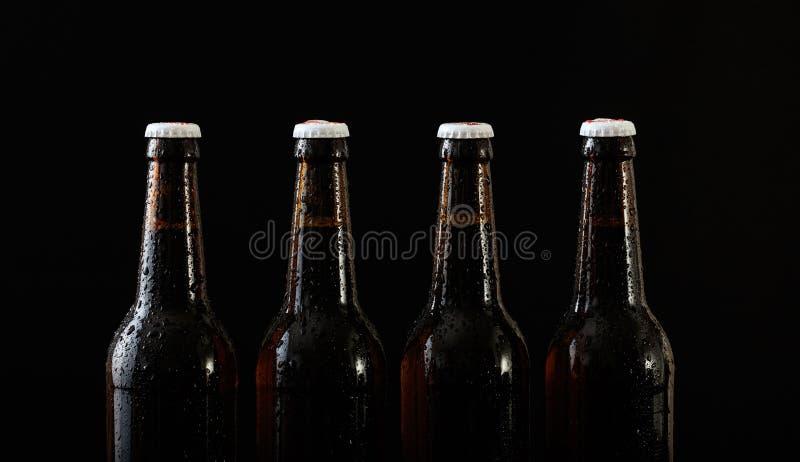 Κινηματογράφηση σε πρώτο πλάνο τεσσάρων μπουκαλιών μπύρας που απομονώνονται στο μαύρο υπόβαθρο απεικόνιση αποθεμάτων