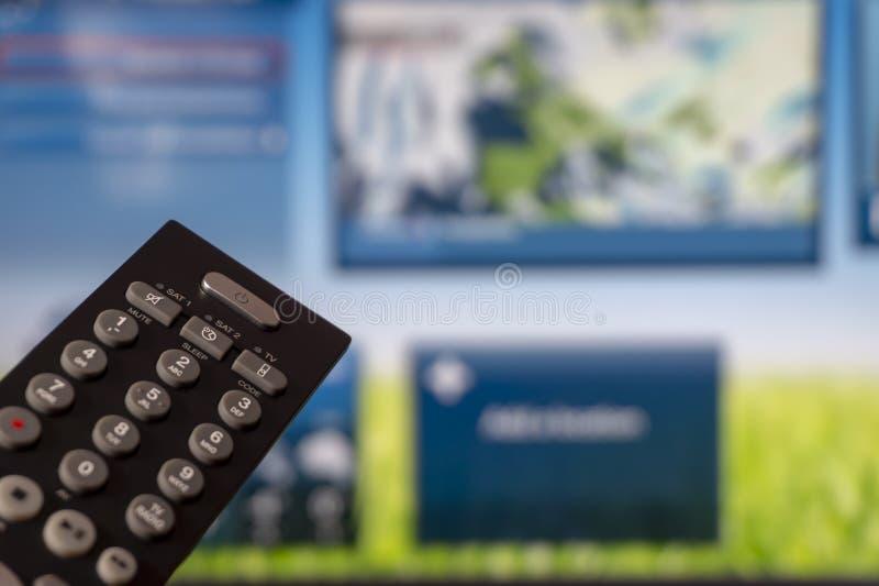 Κινηματογράφηση σε πρώτο πλάνο της έξυπνης TV τηλεχειρισμού και προσοχής στοκ εικόνα