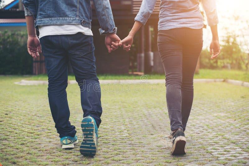 Κινηματογράφηση σε πρώτο πλάνο της αγάπης των χεριών εκμετάλλευσης ζευγών περπατώντας υπαίθριος, Γ στοκ εικόνες