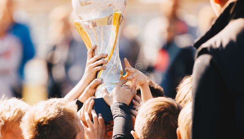 Κινηματογράφηση σε πρώτο πλάνο της αθλητικής ομάδας παιδιών με το τρόπαιο Αγόρια που γιορτάζουν το αθλητικό επίτευγμα Αθλητικοί π στοκ φωτογραφίες με δικαίωμα ελεύθερης χρήσης