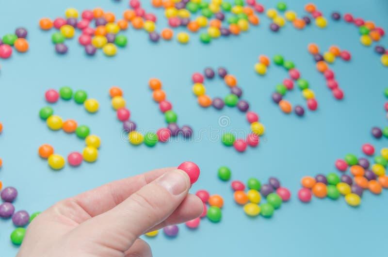 Κινηματογράφηση σε πρώτο πλάνο της διατροφής ζάχαρης καραμέλας καραμελών που σχεδιάζεται, στο μπλε υπόβαθρο στοκ εικόνα