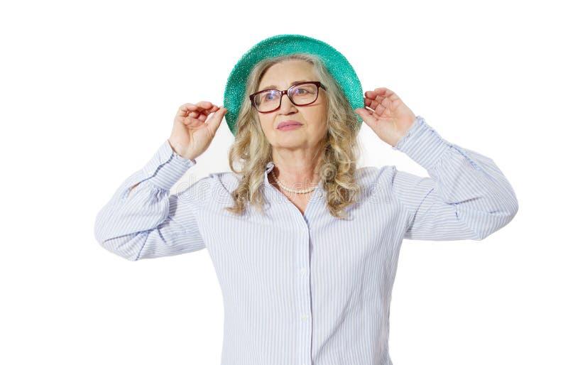 Κινηματογράφηση σε πρώτο πλάνο της ευτυχούς μοντέρνης ανώτερης γυναίκας στα επιχειρησιακά γυαλιά και το θερινό καπέλο Θετική διαβ στοκ εικόνες