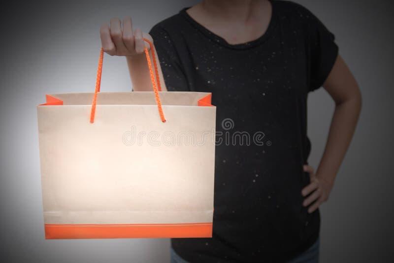 Κινηματογράφηση σε πρώτο πλάνο της θηλυκής τσάντας αγορών εγγράφου εκμετάλλευσης πελατών στο γκρίζο υπόβαθρο Έννοια συμπεριφοράς  στοκ εικόνα