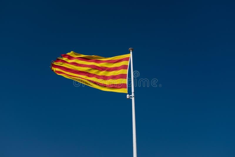 Κινηματογράφηση σε πρώτο πλάνο της καταλανικής σημαίας που πετά στο μπλε ουρανό στοκ εικόνες