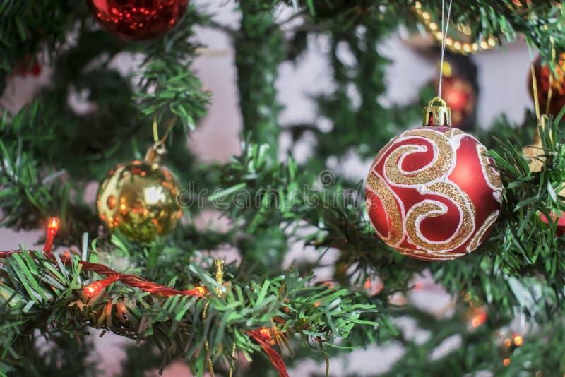 Κινηματογράφηση σε πρώτο πλάνο της κόκκινης ένωσης μπιχλιμπιδιών από ένα διακοσμημένο χριστουγεννιάτικο δέντρο στοκ φωτογραφίες