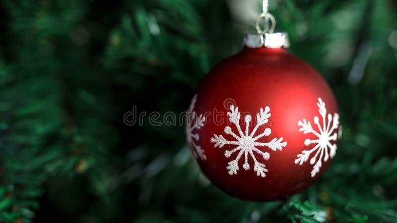 Κινηματογράφηση σε πρώτο πλάνο της κόκκινης ένωσης μπιχλιμπιδιών στα διακοσμημένα Χριστούγεννα και το νέο δέντρο έτους στοκ φωτογραφίες