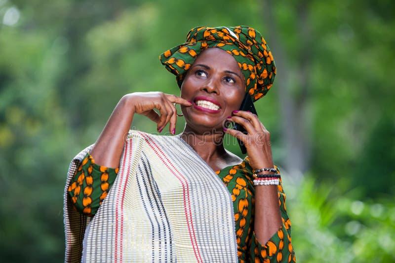 Κινηματογράφηση σε πρώτο πλάνο της νέας αφρικανικής γυναίκας με το κινητό τηλέφωνο, ευτυχής στοκ εικόνες