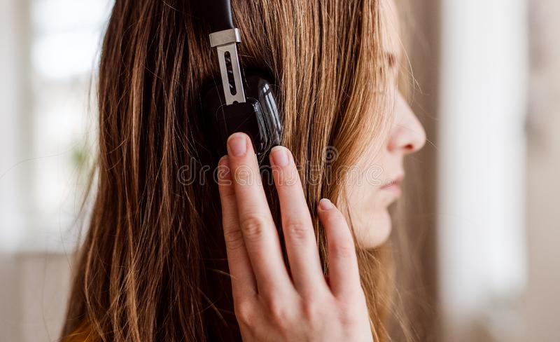Κινηματογράφηση σε πρώτο πλάνο της νέας γυναίκας σπουδαστή με τα ακουστικά, πλάγια όψη στοκ φωτογραφία με δικαίωμα ελεύθερης χρήσης
